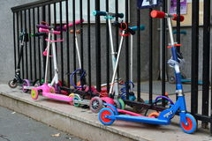 Kids roller scooters parked against iron fence stock photo