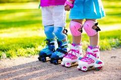 Kids roller skating in summer park Royalty Free Stock Image