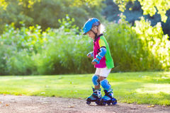 Kids roller skating in summer park Stock Photos