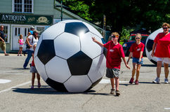 Kids rolling giant soccer balls Royalty Free Stock Image