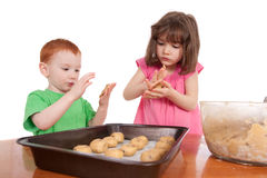 Kids rolling out chocolate chip cookies for baking Stock Image