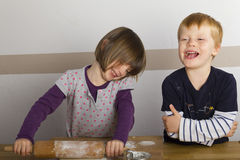 Kids rolling out dough with a rolling pin Stock Photo