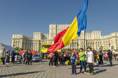 Kids with Romanian flag. Kids holding and waving a big Romanian flag in front of the Bucharest Palace of Parliament on October 05, 2014 in Bucharest, Romania Stock Images