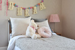 Kids room with doll and pillows on bed Stock Photo