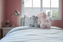 Kids room with dolls and pillows on bed and bedside table lamp Stock Images
