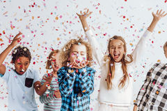 Kids in a room full of confetti. Happy kids having fun in a room full of confetti royalty free stock photo