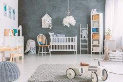 Kids room with grey wall. Cosy kids room with grey wall and a cot stock photography