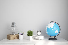 Kids room or home office white table. Interior of a kids room with a white wooden table, an oil lamp, an alarm clock and a globe. Elements of this image Stock Image