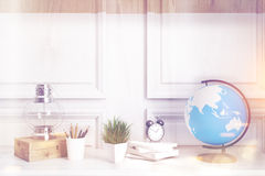 Kids room or home office white table, wood toned. Interior of a kids room with a white wooden table, a wooden wall, an oil lamp, an alarm clock and a globe Royalty Free Stock Photos