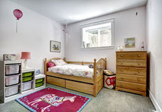 Kids room interior with storage baskets for toys. Cozy kids room with rustic bed and dresser. Cheerful red rug on carpet floor Stock Images