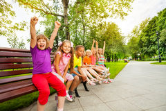Kids in row on bench with some mates excited. Who hold arms up straight in the air Royalty Free Stock Images