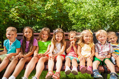 Kids in row on the bench, summer park Royalty Free Stock Photos