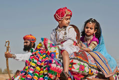 Kids from a royal family drive to the Desert Festival. JAISALMER, INDIA: Unidentified boy and girl like a royal family sitting on the camel back and drive to the royalty free stock images