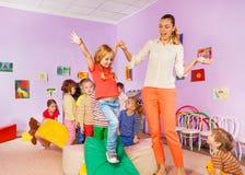 Kids run, climb around soft block in active class Stock Photos