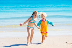 Kids run and play on tropical beach. Happy kids play, run and jump in sand on tropical beach on exotic summer vacation. Boy and girl playing in ocean water. Sea Stock Photos