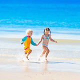 Kids run and play on tropical beach Stock Images
