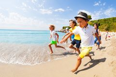 Kids run a race in shallow sea water Royalty Free Stock Image