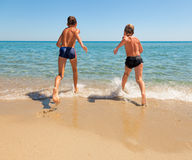 Kids run to the sea Stock Image
