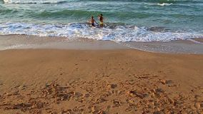 Kids run to swim in the sea stock footage