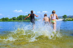 Kids run into in water royalty free stock photography