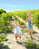 Kids running across field outdoor. Royalty Free Stock Photo