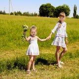 Kids running across green grass outdoor. Royalty Free Stock Photo