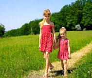 Kids running across green grass outdoor. Royalty Free Stock Photography