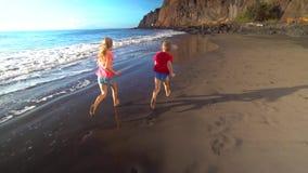 Kids running along the beach. Two kids running along the beach stock video footage