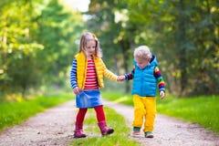 Kids running in autumn park Stock Photos