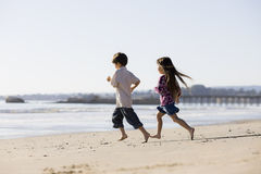 Kids Running on Beach Stock Images