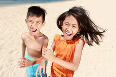 Kids running in the beach. Portrait of happy little boy and girl running in the beach together Royalty Free Stock Photography