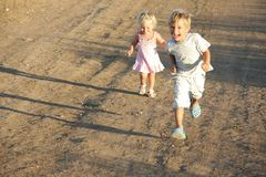 Kids running by country road Stock Images