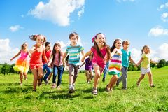 Kids running enjoying summer. Many different kids, boys and girls running in the park on sunny summer day in casual clothes Stock Photo
