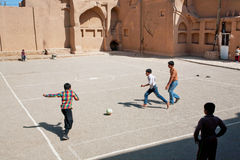 Kids running on football playground on Middle Eastern street Stock Images
