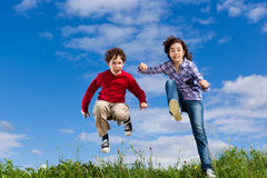 Kids running, jumping outdoor. Girl and boy running against blue sky Royalty Free Stock Image