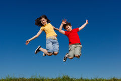 Kids running, jumping outdoor. Girl and boy running against blue sky Royalty Free Stock Photography