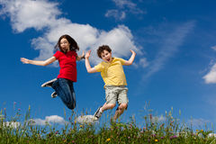 Kids running, jumping outdoor. Girl and boy running against blue sky Royalty Free Stock Photo