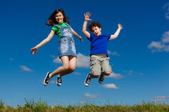 Kids running, jumping outdoor. Girl and boy running against blue sky Royalty Free Stock Photos
