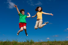 Kids running, jumping outdoor. Girl and boy running against blue sky Stock Images
