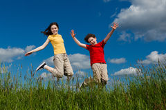 Kids running, jumping outdoor. Girl and boy running against blue sky Stock Image