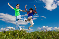 Kids running, jumping outdoor. Girl and boy running against blue sky Stock Photography