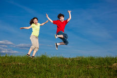 Kids running, jumping outdoor. Girl and boy running against blue sky Stock Photo