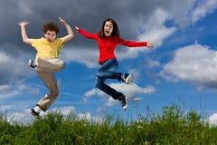 Kids running, jumping outdoor. Girl and boy running against blue sky Stock Photos