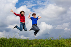 Kids running, jumping outdoor. Girl and boy running against blue sky Royalty Free Stock Images