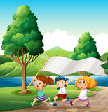 Kids running near the riverbank while bringing an empty banner Royalty Free Stock Photos