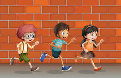 Kids running near wall. Illustration of kids running near a brick wall Stock Photo