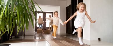 Kids running into new house parents with boxes on background. Horizontal photo happy little kids running into new home, parents with cardboard boxes on royalty free stock image
