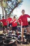 Kids running over tyres during obstacle course training. In the boot camp Stock Photo