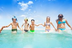 Kids running in the sea together holding hands. Kids in scuba masks running in the sea together holding hands on sky background Royalty Free Stock Photography