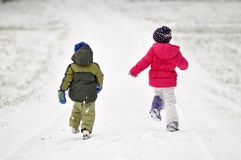 Kids running in snow Stock Image